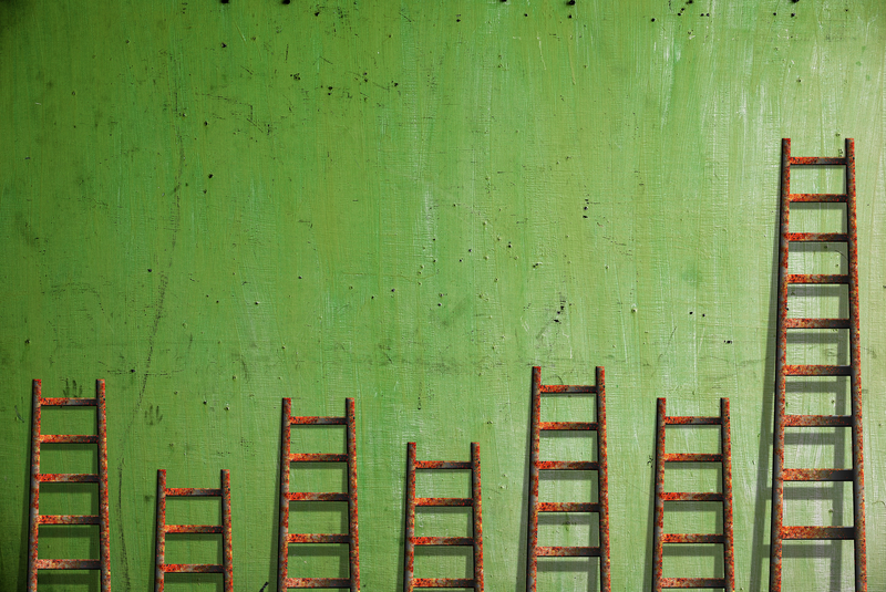 7 ladders leaned up against a green wall