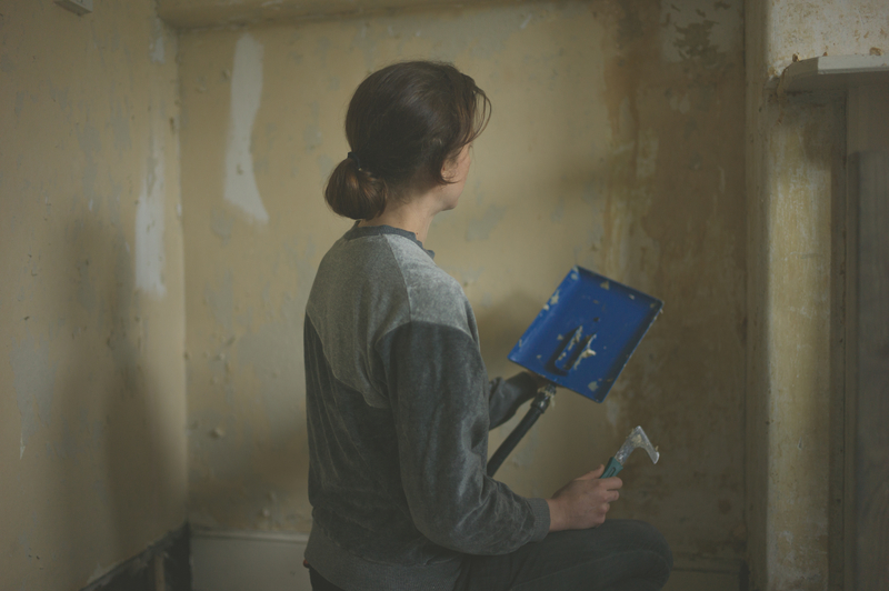woman using a wall paper stripper to remove wallpaper